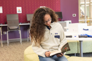 Young girl reading at a Charlotte Mecklenburg Library