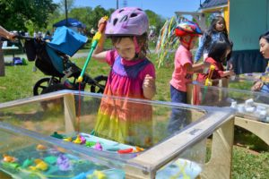 Little girl plays at the tiny house's water table
