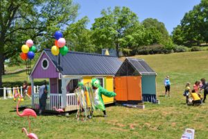 Wide shot of the tiny house with balloons
