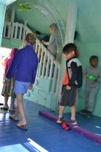 Kids walk through the tiny playhouse