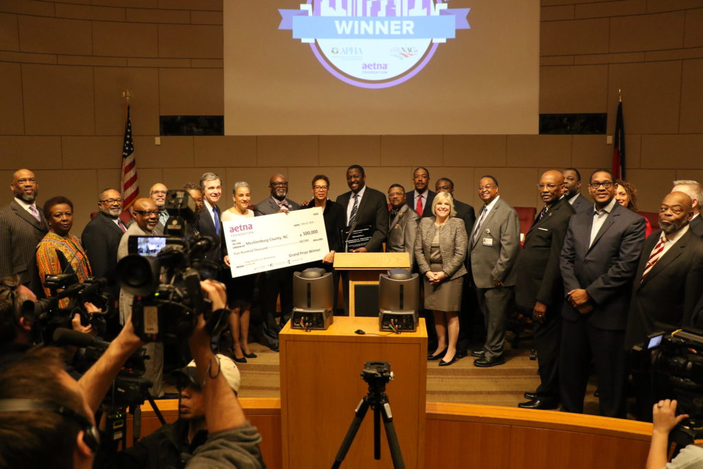 Mecklenburg County's Public Health department, along with Governor Roy Cooper, program participants and community stakeholders, accepts the Healthiest Cities and Counties Challenge grand prize award for the Village HeartBEAT program.
