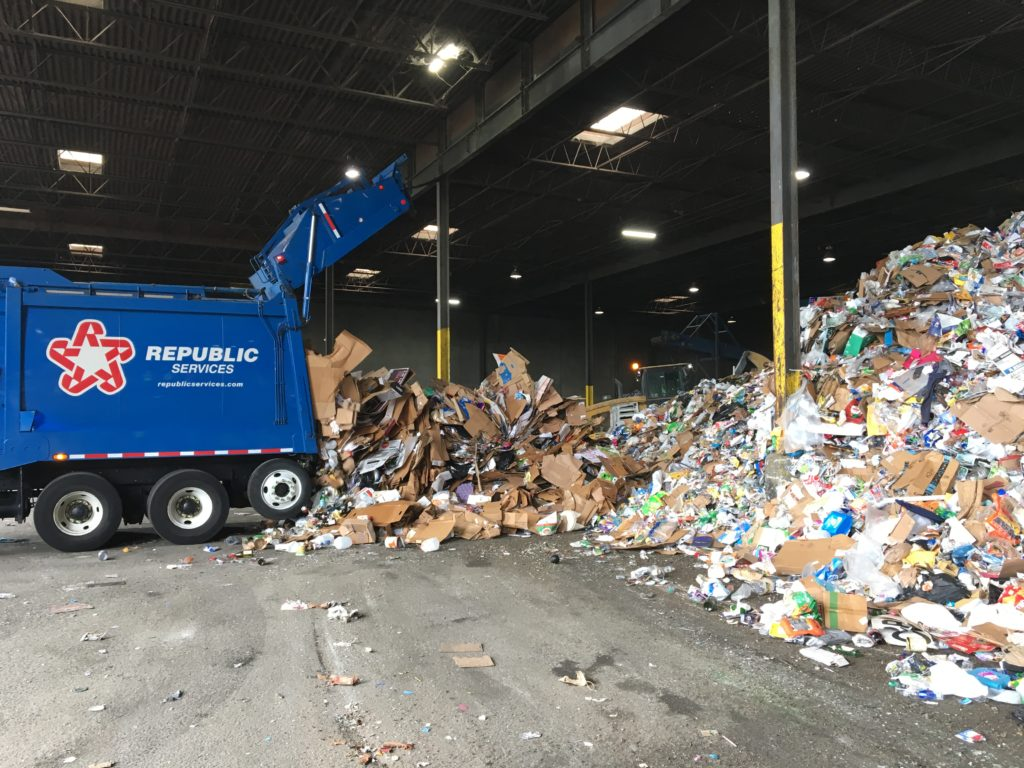 Recycling truck emptying recyclable materials.