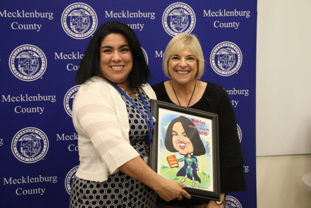 Service Quality winner Monica Madrigal poses with County Manager Dena R. Diorio while accepting her Customer Service Hero Award.