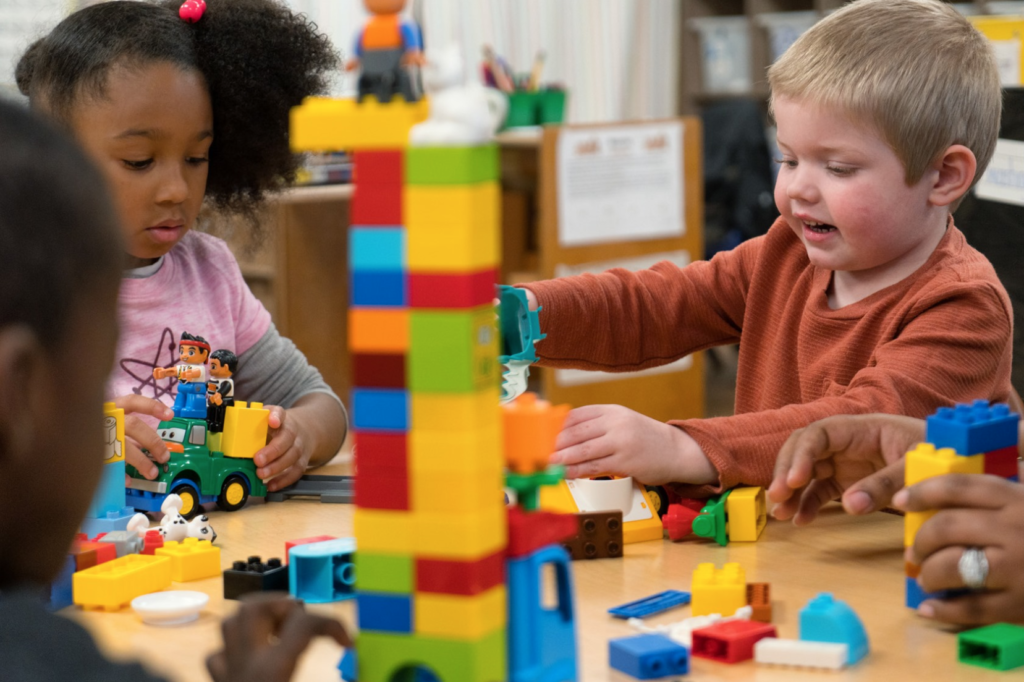 Three pre-k students play and learn with blocks at a table in their classroom.
