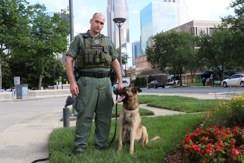 Mecklenburg County Sheriff's Deputy Beckham poses with his K-9 Atos.