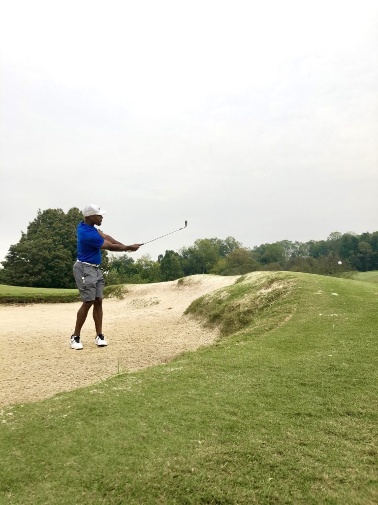 Man golfing from sand trap