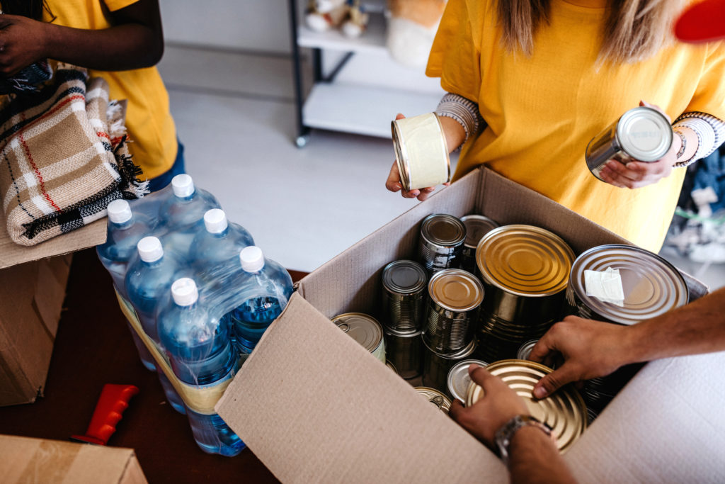 Group of people putting canned goods into boxes to help homeless neighbors