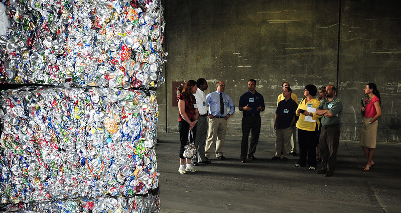 Tour group learns about recycling while standing in front of large bales of crushed metal cans.