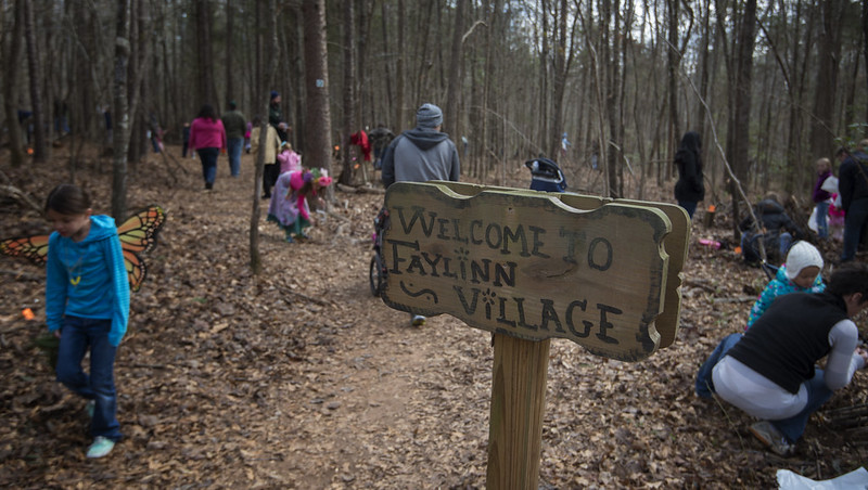 "people walking around in woods near sign ""Welcome to Faylinn Village."""