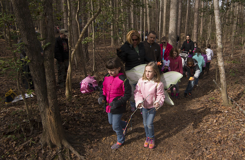 Children marching through the woods, some wearing wings