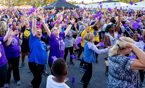 People cheering, throwing purple in the air at a Relay for Life event