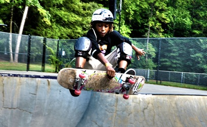 Child wearing protective gear catching air on a skateboard