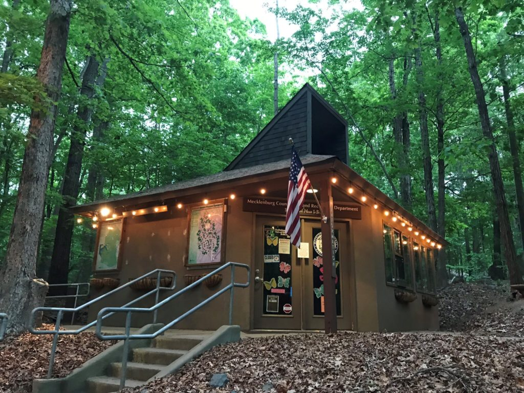 McDowell Nature Center standing among the trees, lit up with string lights and beckoning you to visit during your staycation.