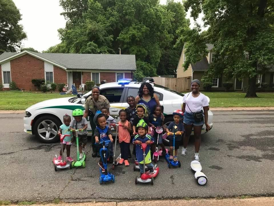Children on scooters and their parents stand in the street with a community engagement officer in front of a Mecklenburg County Sheriff's Office car during National Night Out.