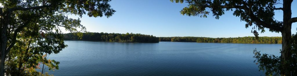 A view of the lake at Latta with green trees in the distance, trees framing the foreground on either side.